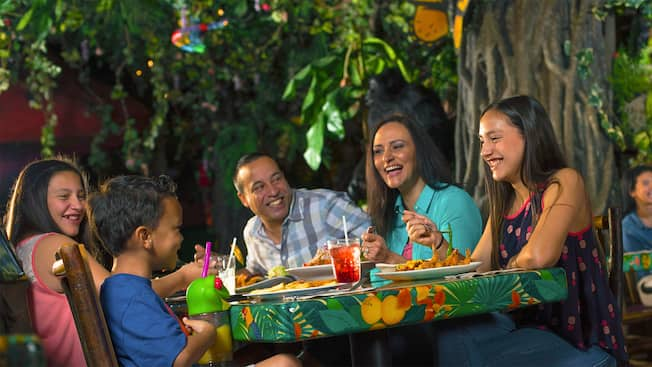 A family of 3 dines at the Rainforest Café at the Disney Springs Marketplace