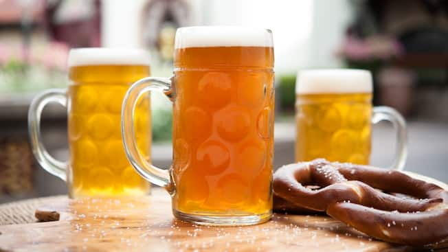 Tall pints of chilled ale served atop a wooden board beside salted, Bavarian-style pretzels