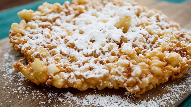 A crispy funnel cake dessert topped with powdered sugar