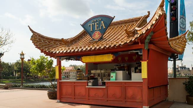 An outdoor kiosk with a sweeping Chinese architecture-inspired roof and a sign that reads 'Joy of Tea'