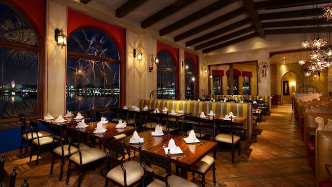 La Hacienda de San Angel dining room with large windows and beamed ceiling, lit up at night