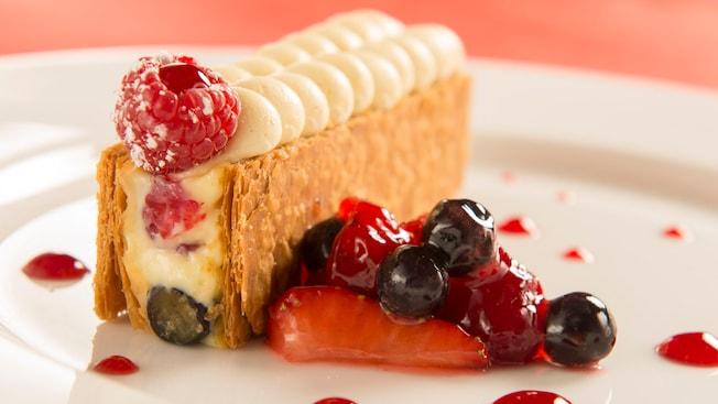 Un plato de postre con Napoleón de frutos rojos con crema ligera de limón y sorbete de fresa