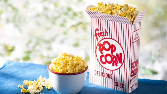 A scattered array of popcorn next to a vintage popcorn box and a small bowl