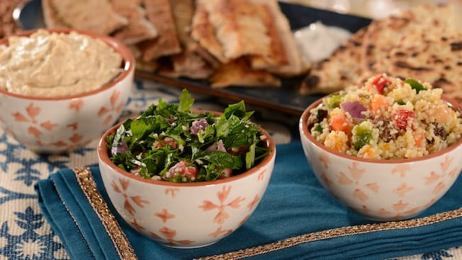 A bowl of hummus, a bowl of salad and a bowl of couscous sit in front of a plate of flatbreads.