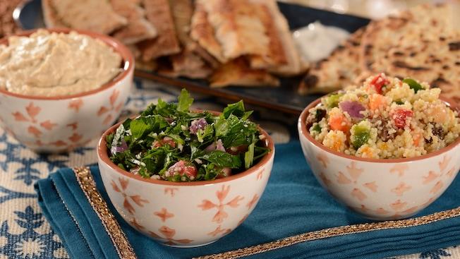 Un tazón de hummus, un tazón de ensalada y un tazón de cuscús frente a un plato de flatbreads.