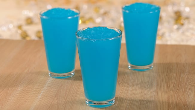 Three pint glasses filled with a blue, icy beverage