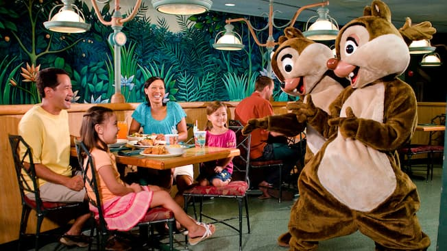 Mickey Mouse in farmer's garb greets Dad, Mom and daughter at Garden Grill