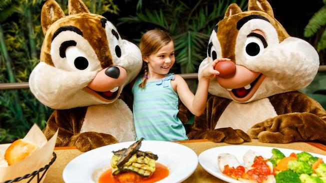 Uma garota entre Chip 'n' Dale, apertando o grande nariz vermelho do Dale no restaurante The Garden Grill