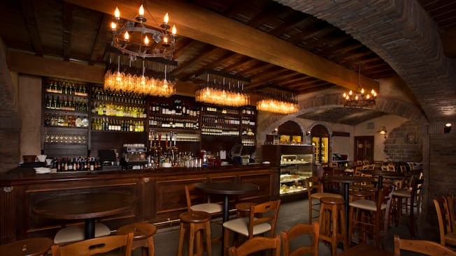 A dark-wood and brick wine cellar with high tables, stools, and a long bar with a wall of wine bottles