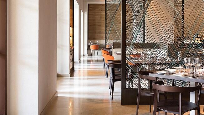 Copas de vino relucientes, cristalería de plata y platos pequeños adornan las mesas, en medio de una decoración moderna