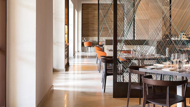 Taças de vinhos reluzentes, taças de prata e pratos delicados adornam as mesas de jantar em meio à decoração moderna