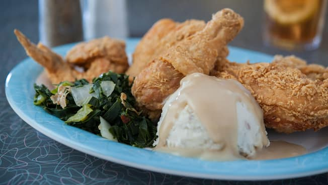 A plate of fried chicken with collard greens, mashed potatoes and gravy