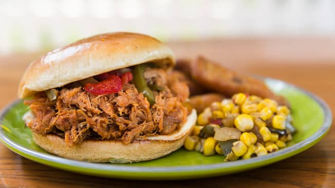 A pulled pork sandwich on a plate with corn salsa and fried plantains