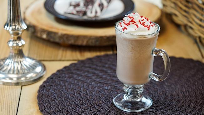 Una copa ornamentada llena de chocolate caliente, y cubierta de crema batida esponjosa y espolvoreo navideño