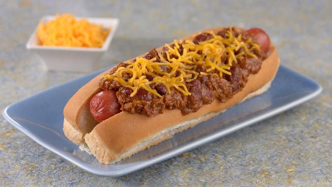 Um cachorro-quente com cobertura de chili e queijo cheddar ralado perto de um prato de queijo cheddar