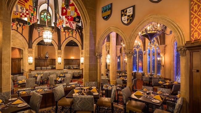 El área de comidas de Cinderella's Royal Table se distingue por sus altas arcadas de piedra y majestuosas ventanas de vitral