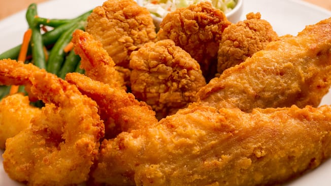 A trio of fried shrimp, breaded chicken and battered fish served alongside green beans and coleslaw