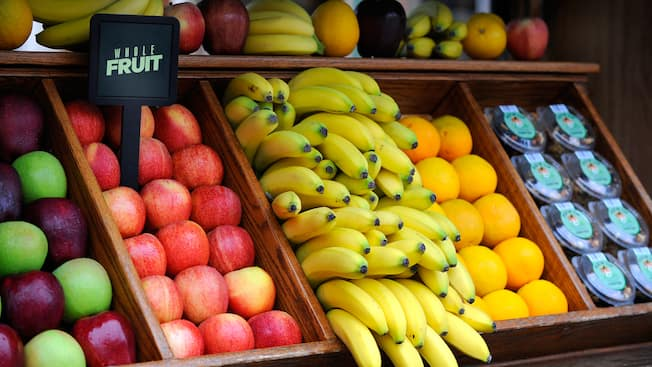 A fruit stand containing fresh apples, bananas, oranges and trail mix