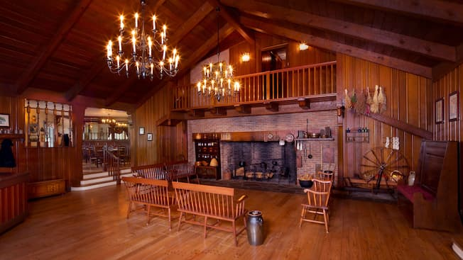 Early American-inspired waiting hall with stone fireplace, benches and chandeliers