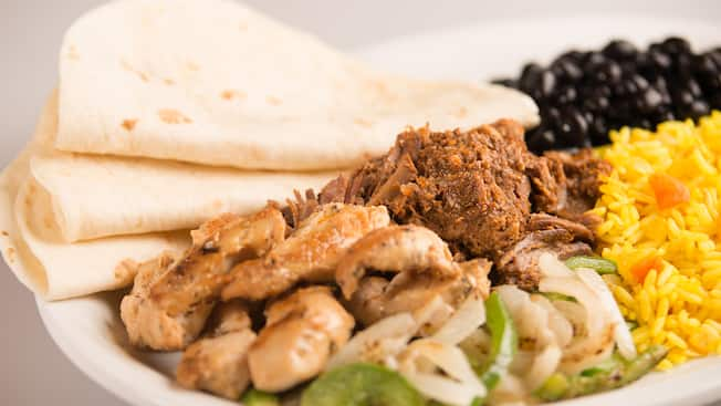 A plate of chicken, bell peppers, black beans and rice