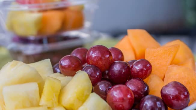 An open container of pineapple chunks, grapes and melon pieces