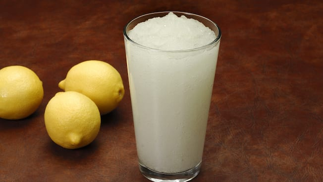 A glass of frozen lemonade sits on a table next to 3 lemons