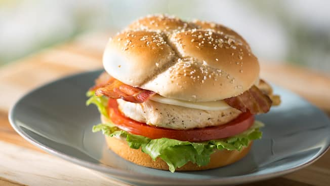 A chicken sandwich with bacon, cheese, tomato and lettuce in a bun