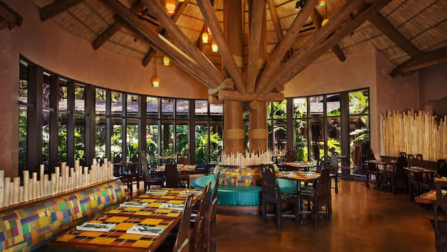 Dining area at Boma—Flavors of Africa, featuring a thatched ceiling and panoramic windows with a garden view