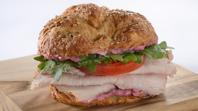 A multi-grain croissant sandwich stuffed with turkey, arugula and tomato