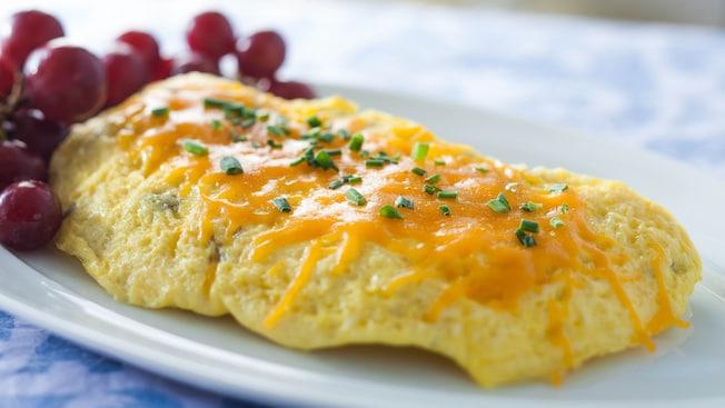 Um omelete coberto com queijo cheddar derretido e cebolinha, acompanhado de uva rosa