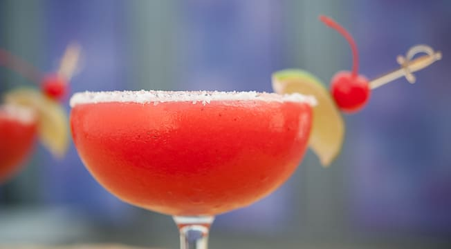 A bright cocktail served in a margarita glass with a salted rim and two lime garnishes