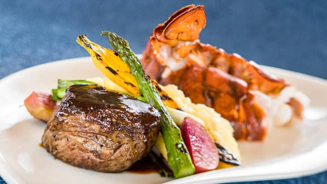 Tenderloin steak next to roasted asparagus, leak, squash, beat, cauliflower and 2 lobster tails on a plate