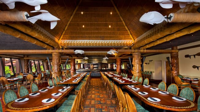 Tropical-themed dining room of 'Ohana at Disney's Polynesian Resort with fire pit in the background