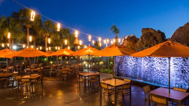 Des lanternes suspendues, des palmiers et une chute d'eau entourent une terrasse extérieure avec des tables et des chaises éclairées la nuit
