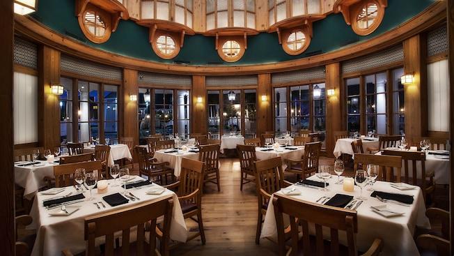 Área de refeições redonda com piso de madeira, teto alto e mesas arrumadas para o jantar