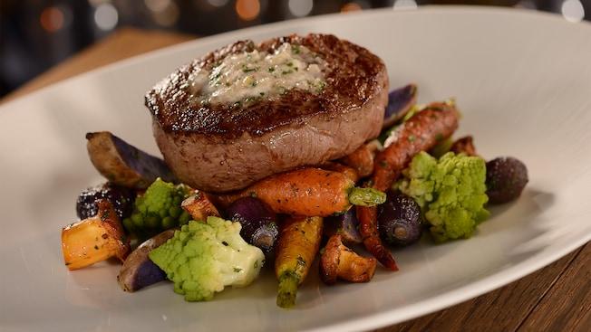 Un filete servido sobre vegetales asados