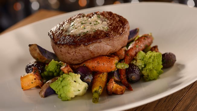 A steak served atop roasted vegetables