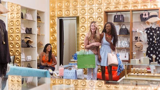 Mulher seleciona bolsas e sorri para duas clientes dentro da Kate Spade New York