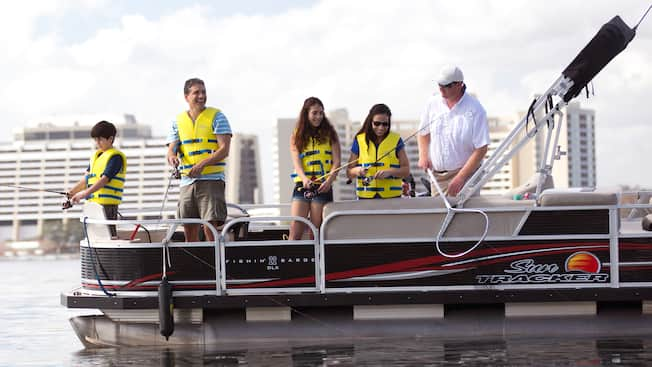 Guests casting their reels into the water from a pontoon boat outside Disney's Contemporary Resort