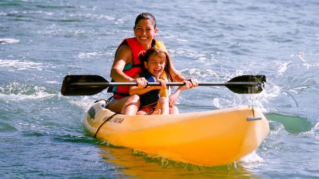 Mother and daughter paddling a kayak on a lake
