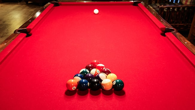 A red pool table with balls racked up and cue ball in position