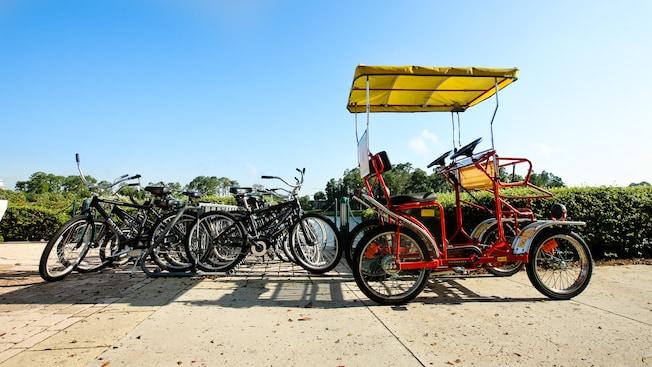 A bikestand with a half dozen bikes plus a Surrey bike