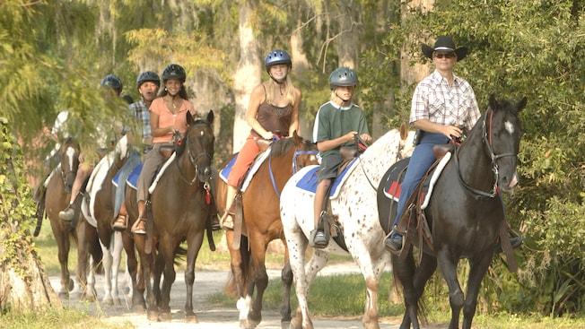 Un grupo de personas montando a caballo por un sendero boscoso