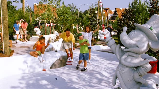 Um menino dá uma tacada na neve artificial no Disney's Winter Summerland Miniature Golf Course