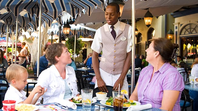 2 women and a child sit at a table and speak with a waiter