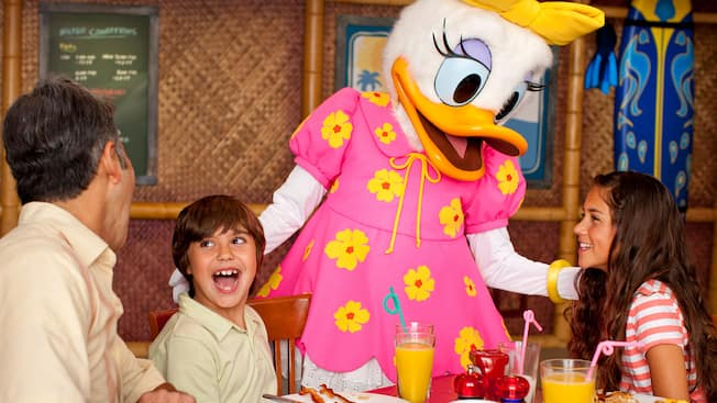 Daisy Duck interacts with a family laughing at a table plated with food