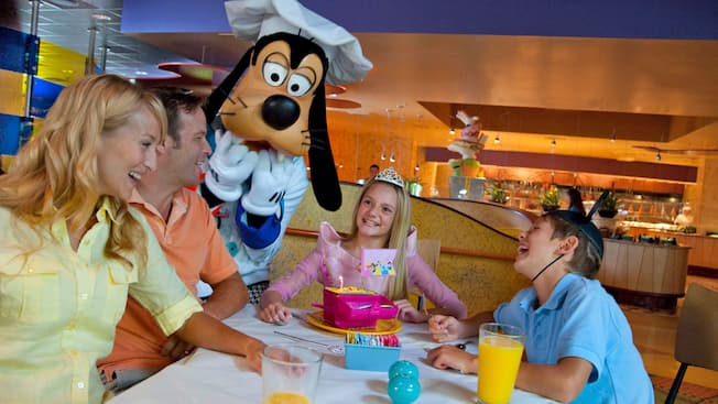 goofy poses next to a smiling family in a restaurant - Goofys Kitchen