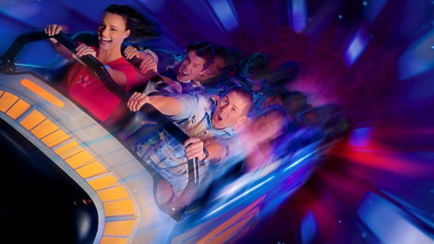 A woman and 2 men scream with delight on Space Mountain as their rocket speeds through outer space