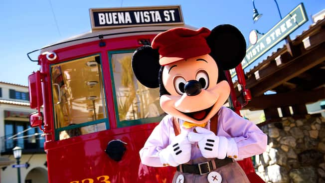 Mickey Mouse stands in front of a trolley with a sign that reads Buena Vista Street