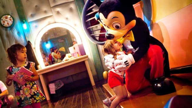 Mickey Mouse hugs a child while a little girl looks on
